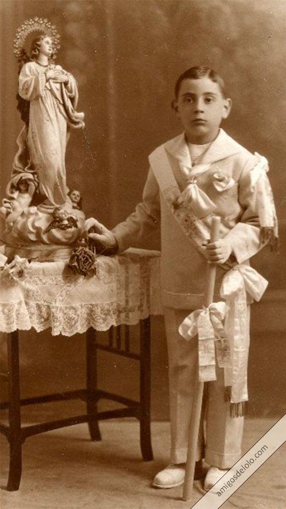Lolo junto a la Virgen sujetando un velón el día de su Primera Comunión